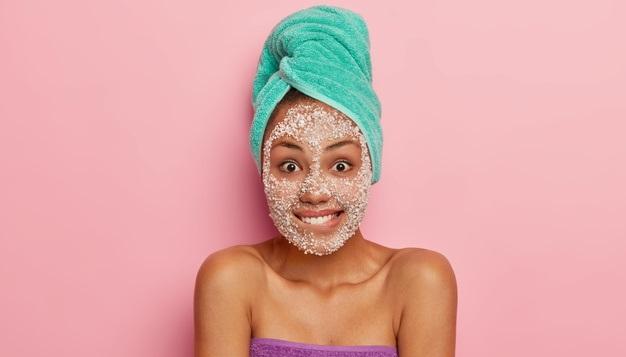 femeie cu masca pentru ten aplicata pe fata si prosop in cap