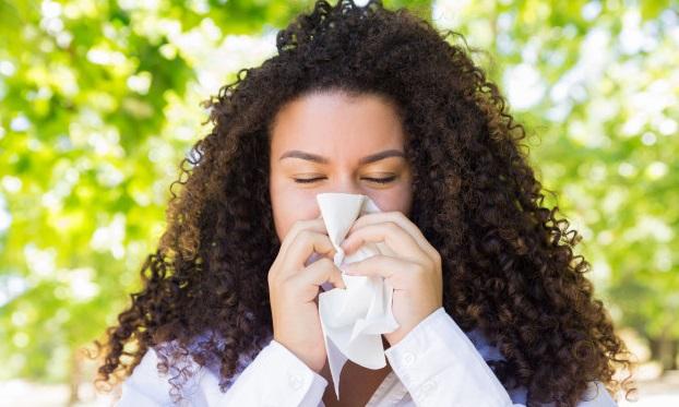 femeie cu parul cret sufla nasul in batista in parc