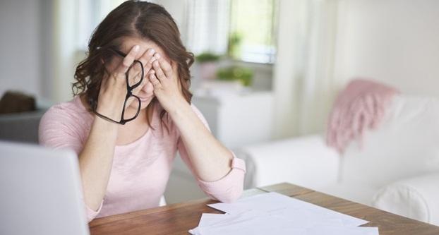 femeie de afaceri stresata se tine cu mainile de cap