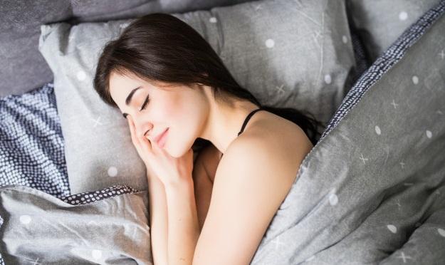 femeie in pat doarme cu mainile sub cap si acoperita cu patura