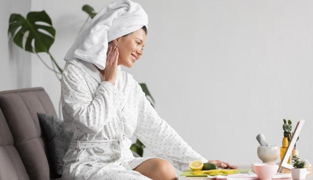 femeie in halat de baie stand la masa si ingrijind pielea fetei