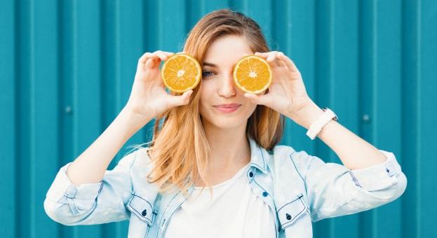 femeie tanara cu doua felii de portocale pe care le tine la ochi