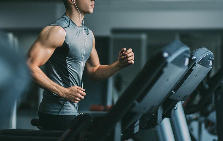 barbat cu muschi alearga pe banda in sala de fitness