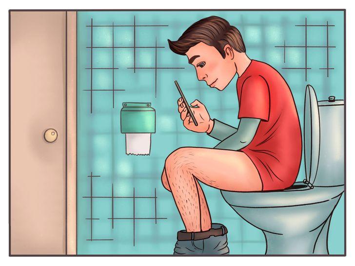 barbat sta pe wc cu tricou rosu si telefon in mana