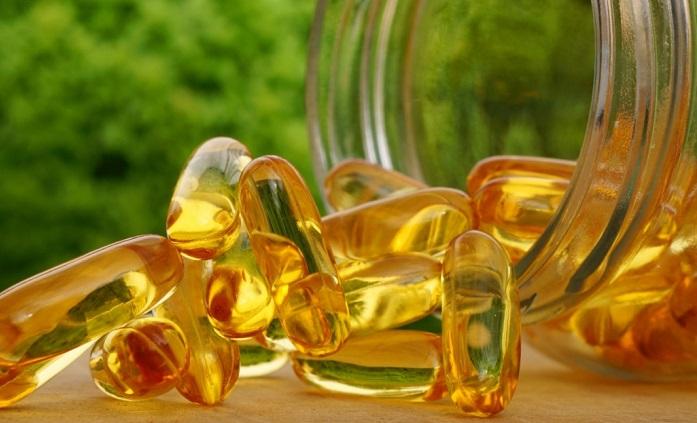 capsule gelationoase transparente cu ulei de peste pe masa borcan de sticla