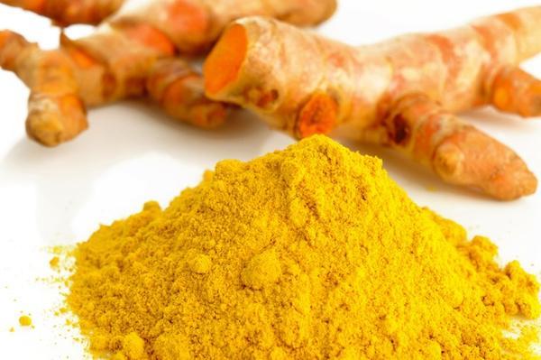pudra de curcumina si radacina de culoare galben aprins