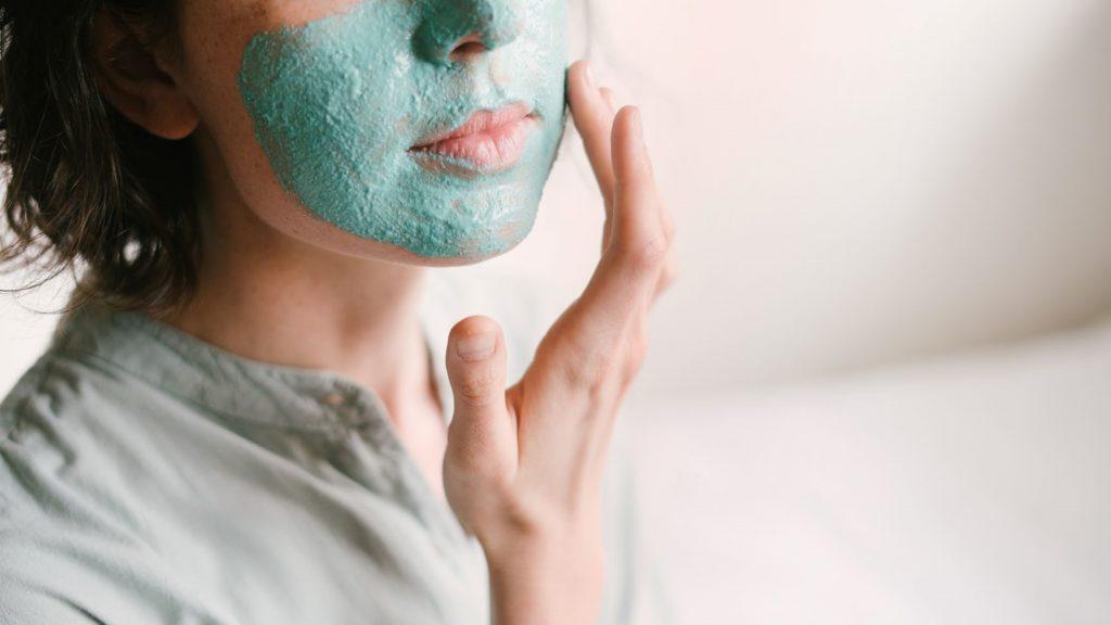 femeie cu parul scurt aplica cu mana masca pentru ten de culoare verde turcoaz
