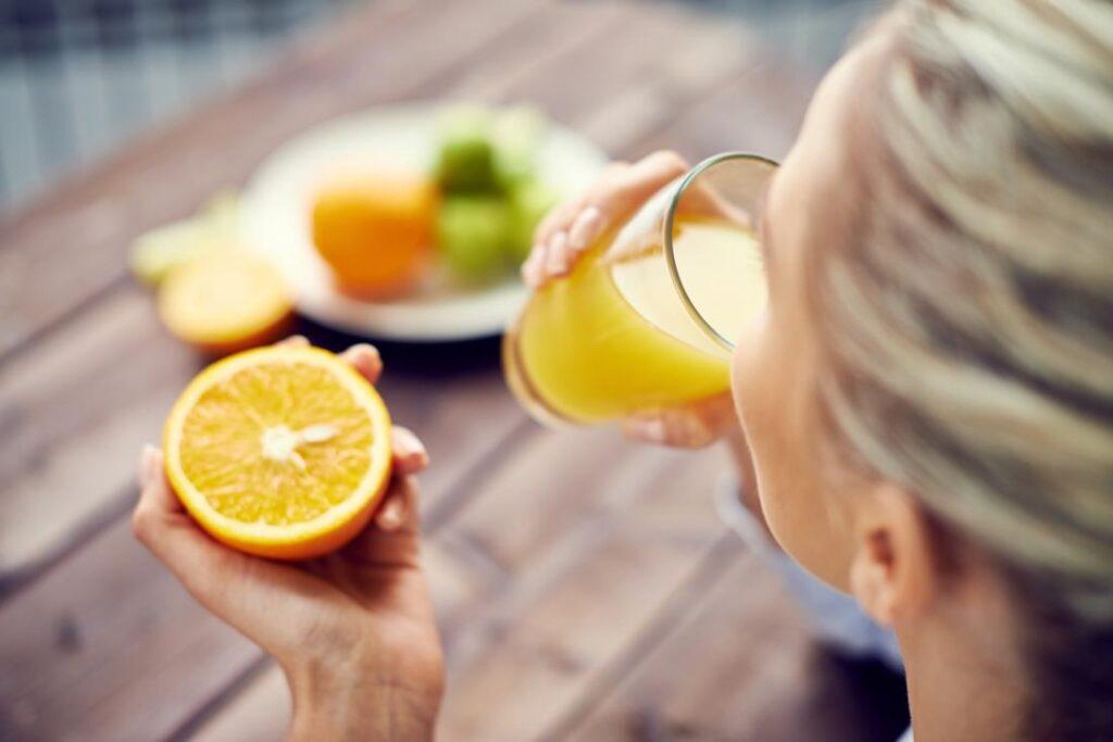 femeie consuma suc de portocale cu vitamina c intr o mana si in cealalta tine o jumatate de portocala