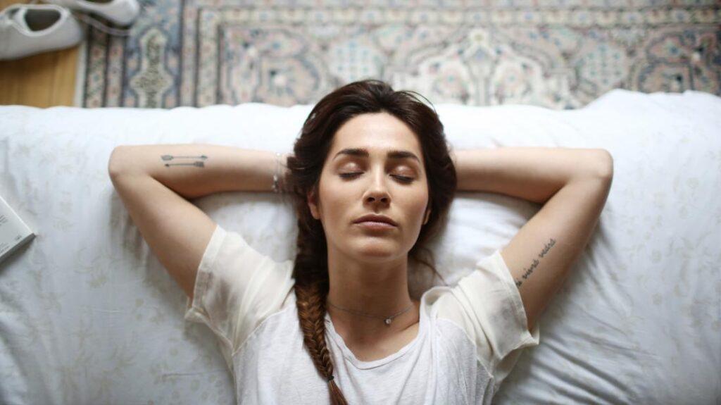femeie relaxata doarme cu mainile sub cap tatuaje pe maini