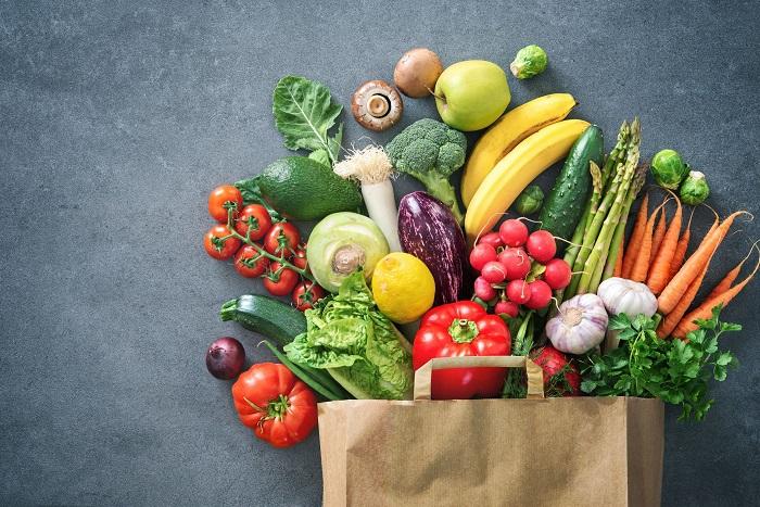 legume si fructe in sacosa de hartie pe fundal gri