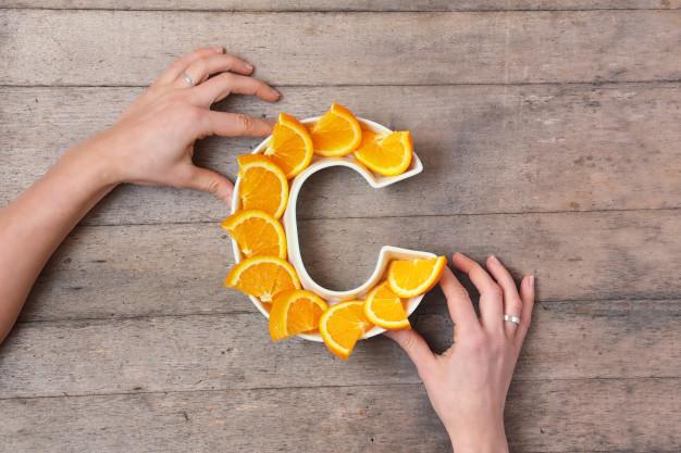 maine femeie formeaza litera c din felii de portocale pe masa de lemn
