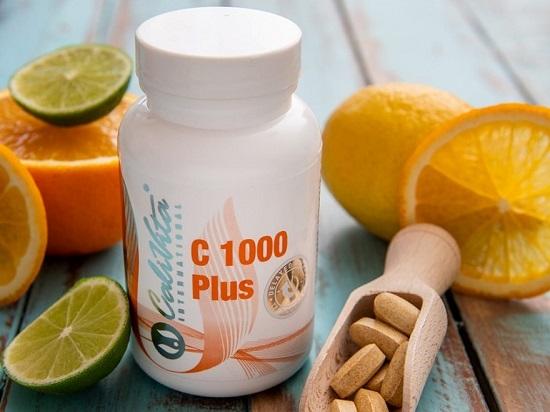 flacon de vitamina c 1000 mg de la calivita pe masa langa felii de portocale