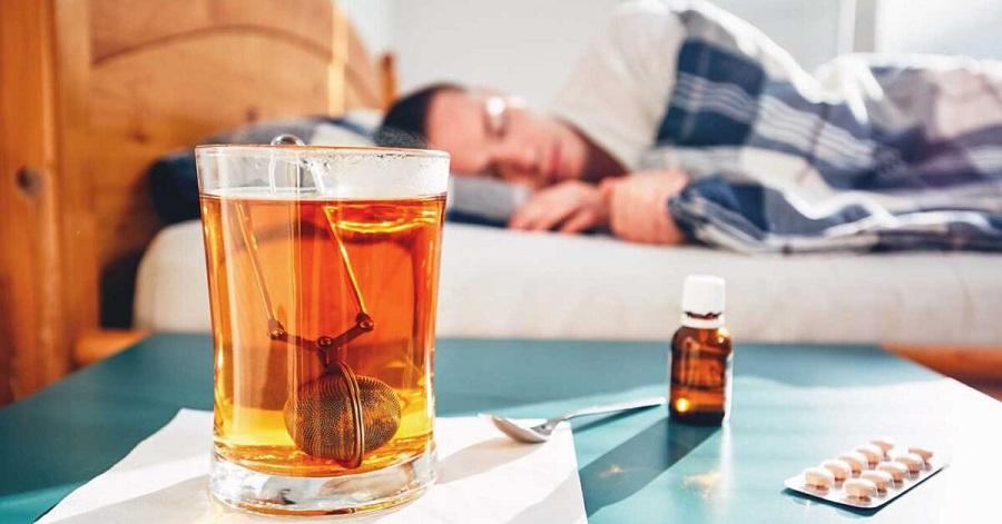 persoana doarme obosita de la febra cu ceai langa el