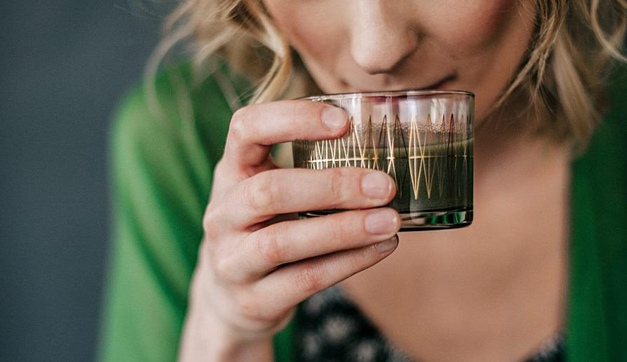 femeie blonda in bluza verde bea clorofila lichida