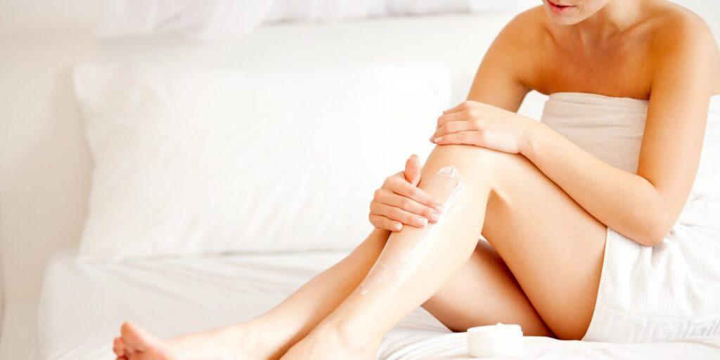 femeie foloseste crema cu uleiul de jojoba pentru corp si masaj picioare